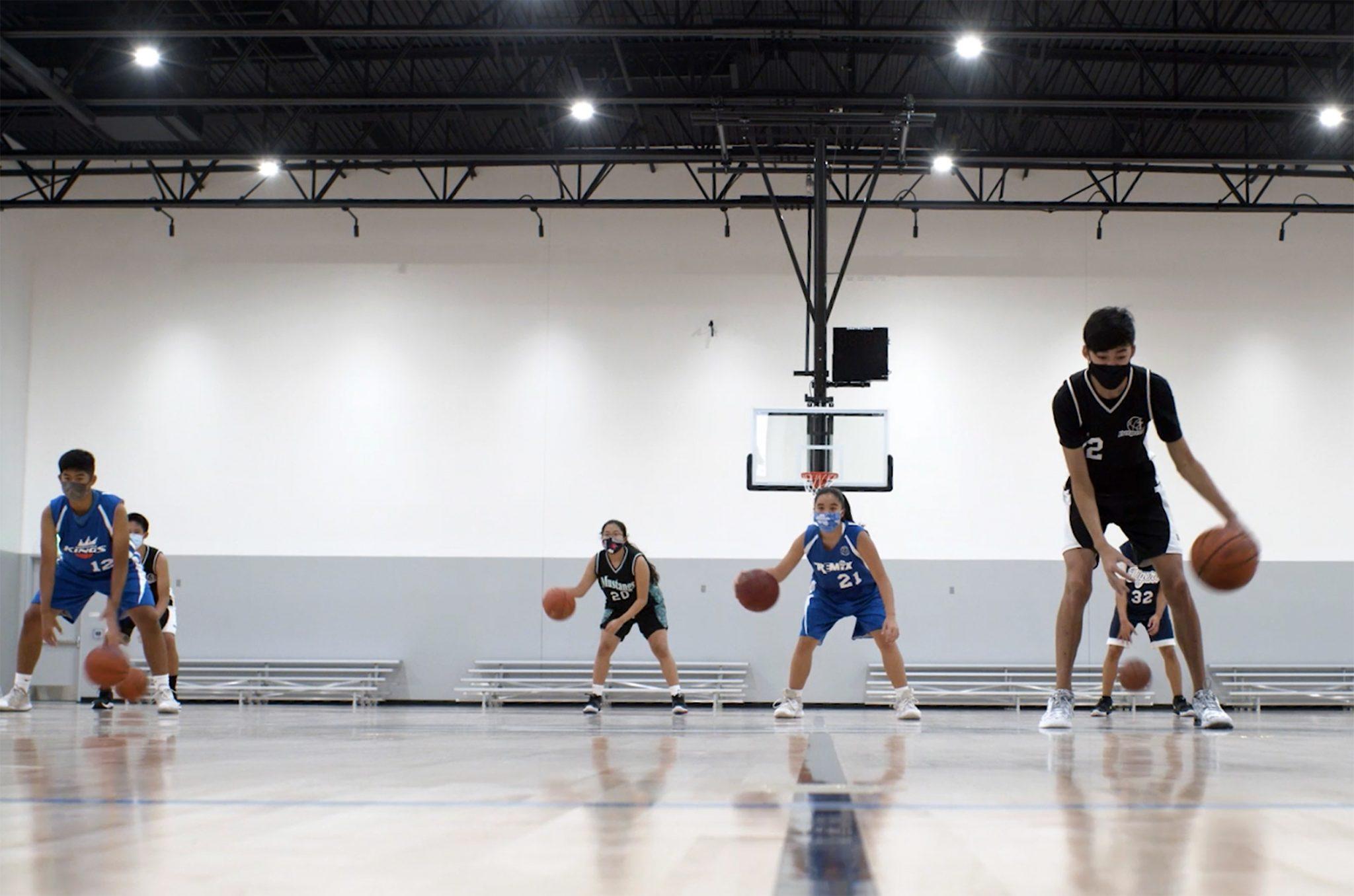 Youth dribbling basketballs in Budokan gym